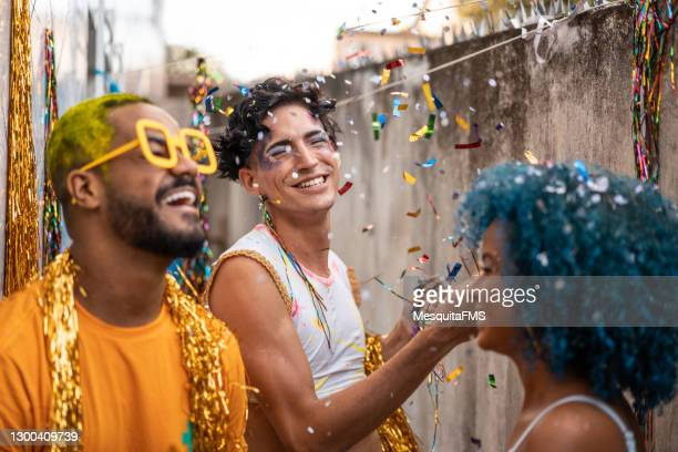people dancing in the rain of confetti at the brazilian carnival - brazilian carnival stock pictures, royalty-free photos & images