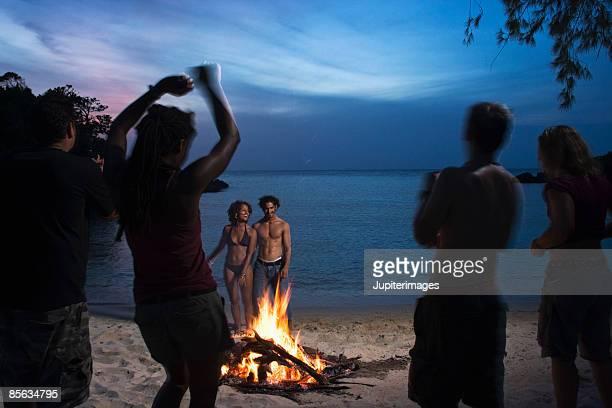 People dancing near bonfire on beach