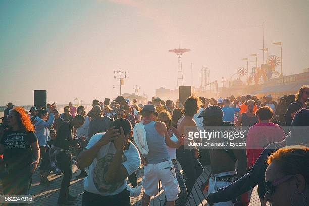 people dancing on floor at coney island against sky - coney island stock pictures, royalty-free photos & images