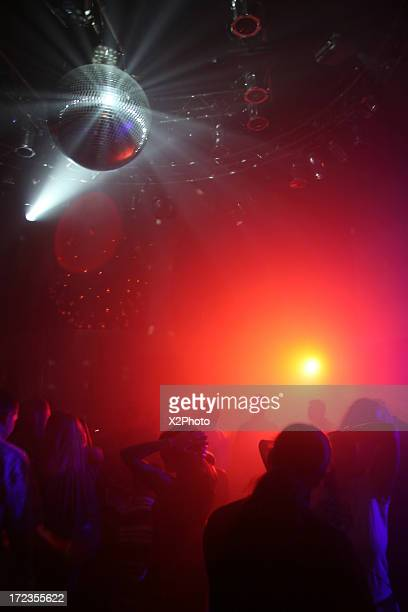People dancing under a disco ball at a nightclub
