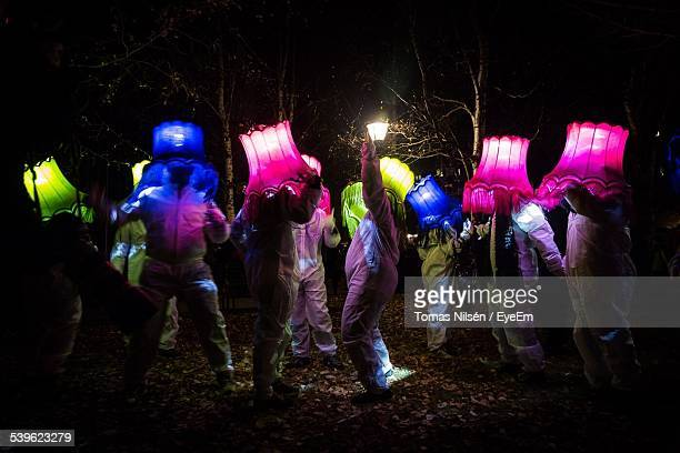 people dancing with lamp shades on head during light festival - nur erwachsene stock-fotos und bilder