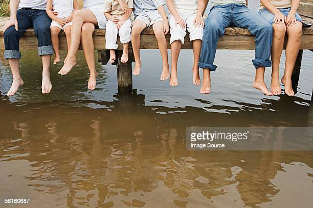 People dangling their feet off a pier
