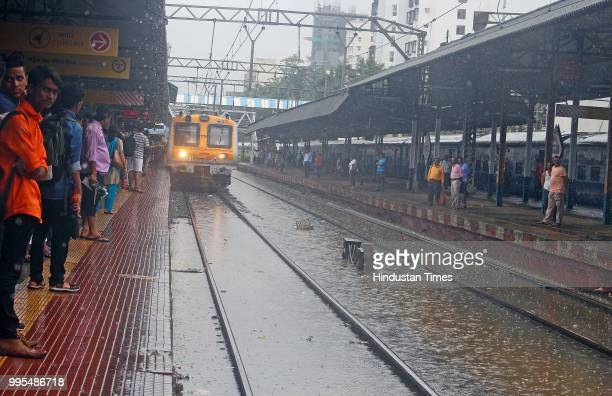 People deal with heavy rain and water logging at Matunga Station on July 9 2018 in Mumbai India Indias financial capital and its surrounding...