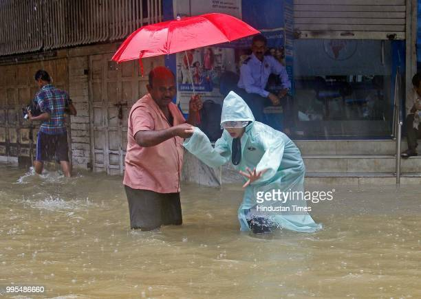 People deal with heavy rain and water logging near Z bridge Matunga Station on July 9 2018 in Mumbai India Indias financial capital and its...
