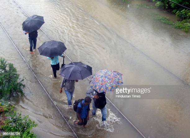 People deal with heavy rain and water logging on tracks at Matunga Station on July 9 2018 in Mumbai India Indias financial capital and its...