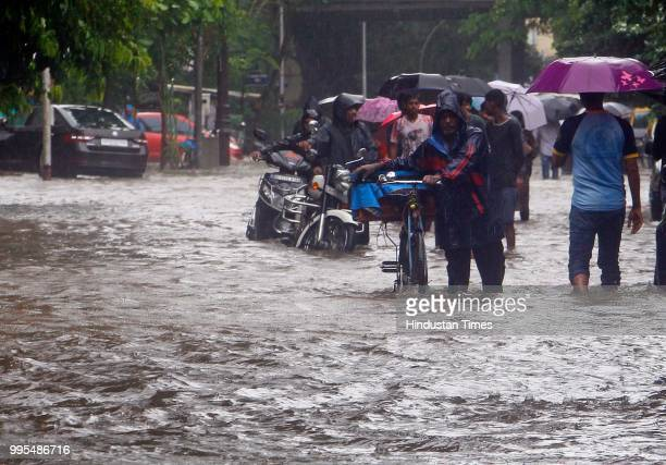 People deal with heavy rain and water logging towards Dadar East Station on July 9 2018 in Mumbai India Indias financial capital and its surrounding...