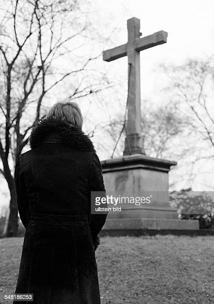 People, death, mourning, churchyard, young woman stands in front of a memorial cross, aged 25 to 30 years, Monika -