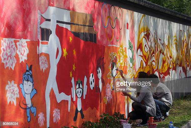 People decorate a wall with colorful graffiti during an activity to celebrate the upcoming 100-day-countdown to the 2008 Beijing Olympics, which will...