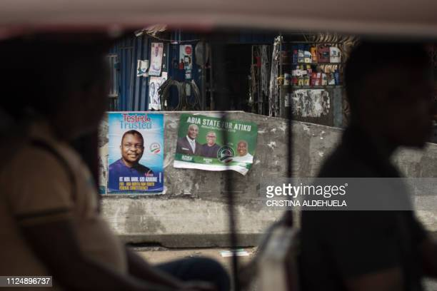 TOPSHOT People Democratic Party candidate posters adorn a wall in Aba a city in one of the proBiafran separatist regions on February 14 2019...