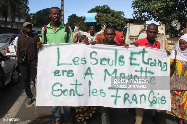 People demonstrate by the French Embassy as they hold antiFrench placard reading 'The only foreigners in Mayotte are the French' in protest to the...