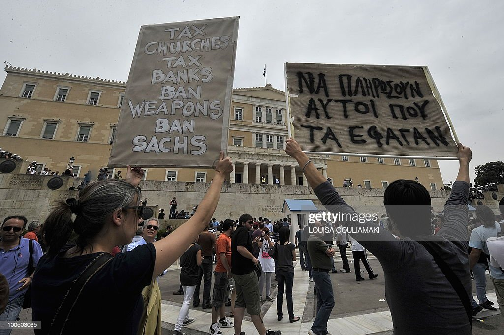 People demonstrate in front of the Greek Parliament during a massive demonstration on May 5, 2010 in Athens.Three people were killed in a firebomb attack on a bank in central Athens on May 5 and around 20 people were evacuated from the building.
