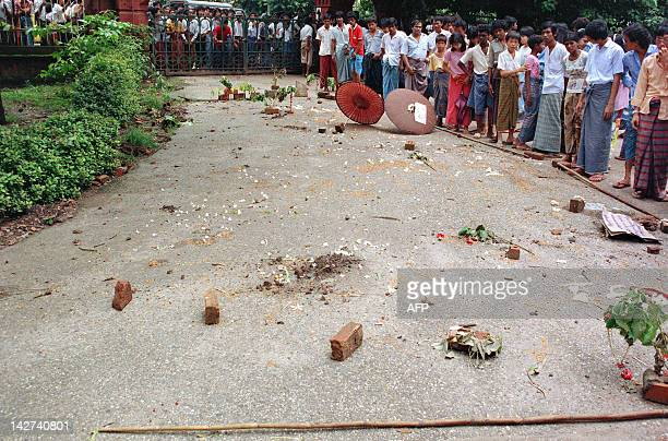 People demonstrate in the street 13 August 1988 in the aftermath of one of worst uprisings in front of bricks which mark where protesters were killed...