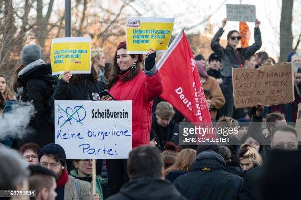 People demonstrate outside Thuringia's State parliament building with yellow placards reading Better to rule with fascists than not to rule Free...