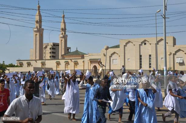 People demonstrate past the Saudi Mosque on November 10 2017 in Nouakchott against a justice ruling after Mauritanian prosecutors said they had...