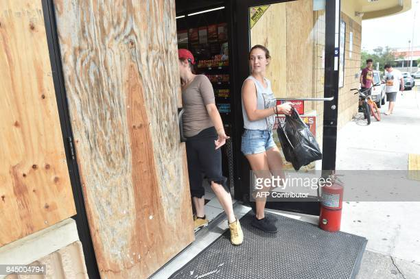 People depart a boarded convenience store as Hurricane Irma approaches September 9 2017 in Port Charlotte Florida Hurricane Irma weakened slightly to...