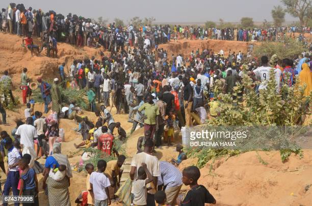 People dig in the soil as hundreds of people search gold on April 25 2017 in KafaKoira south of Niamey Hundreds of people sometimes whole families...
