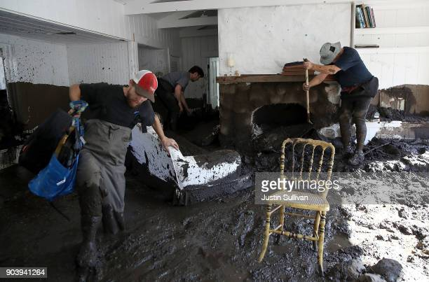 People dig through mud as they look for salvageable items in a the home of a family member that was destroyed by a mudslide on January 11 2018 in...