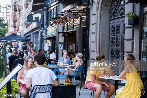 People dine al fresco, or open air, in the East Village on July 21, 2020 in New York City. New York City's Open Restaurant Program, which seeks to...