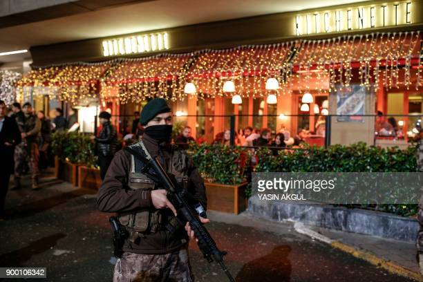 People dine as Turkish security officers patrol around the city's main Taksim Square as people remember the victims of a deadly New Year's attack a...