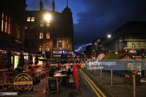 People dine at outdoor tables in the city centre of Manchester, north west England on October 8, 2020. - Pubs and restaurants in coronavirus hotspots...