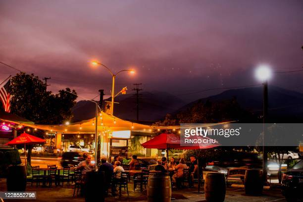 People dine at tables set up in the parking lot of a restaurant as smoke rises from the Bobcat Fire burning in the San Gabriel mountains in the...