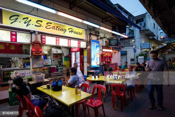 People dine outside at a restaurant in the Little India area of Singapore on Wednesday June 13 2018 Tourism as well as the consumer sector will...