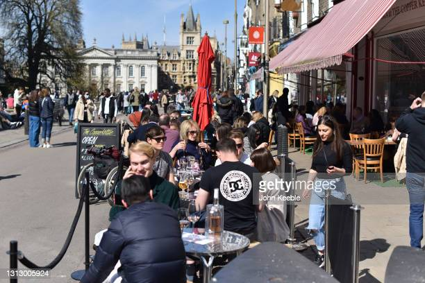 People dine outside in the sun on the first weekend since the easing of lockdown restrictions on April 17, 2021 in Cambridge, England. England has...