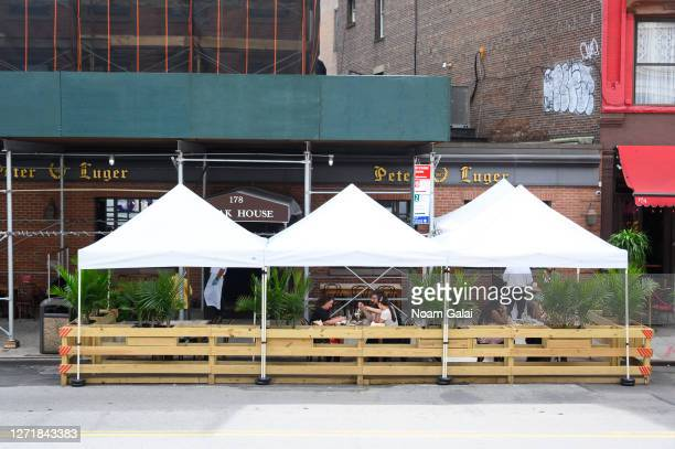 People dine outside Peter Luger Steakhouse in Williamsburg as the city continues Phase 4 of re-opening following restrictions imposed to slow the...