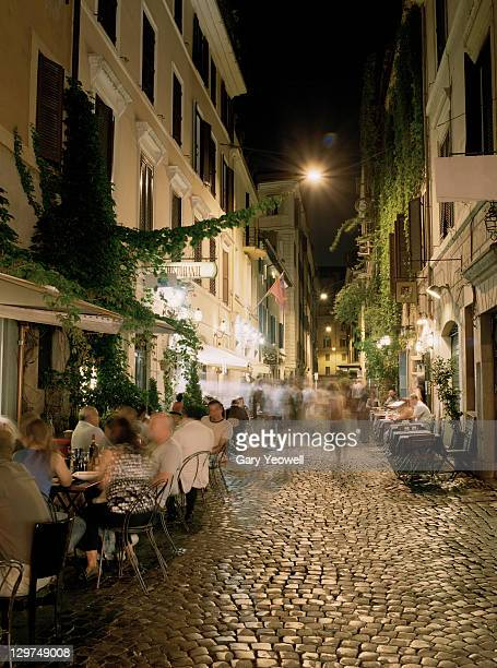 People dining along cobbled street at night