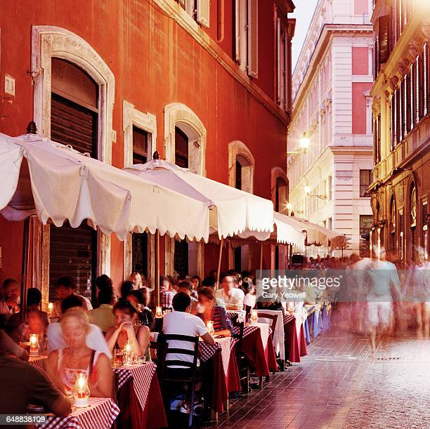 People dining along narrow street at dusk