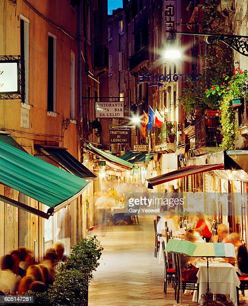 people dining along narrow street at night - atmospheric mood stock pictures, royalty-free photos & images
