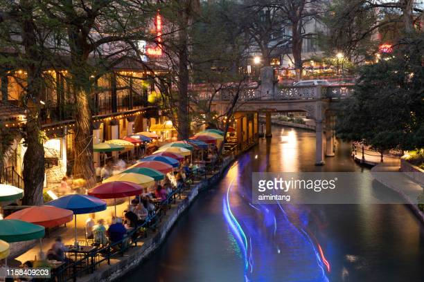 people dining in restaurants along river walk in downtown san antonio - san antonio river walk stock pictures, royalty-free photos & images