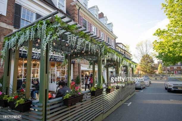 プリンストンのダウンタウンで屋外で食事をしたり、歩道を歩いたりする人 - ニュージャージー州 プリンストン ストックフォトと画像