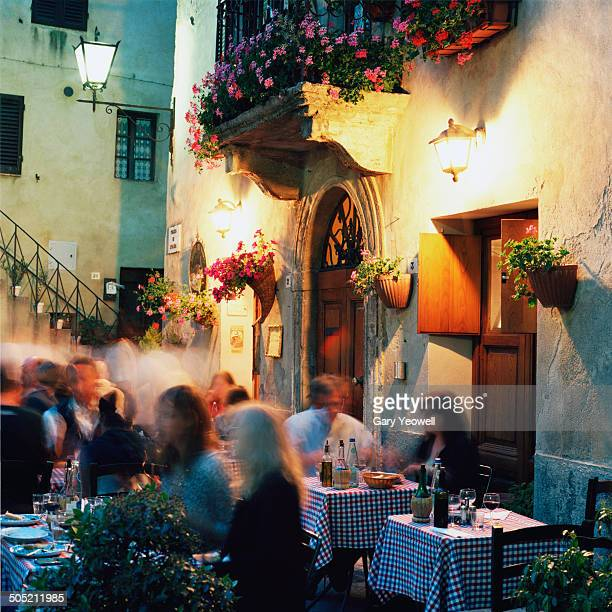 people dining outside a restaurant at night - italy stock-fotos und bilder