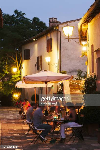 people dining outside restaurants at dusk - italy stock pictures, royalty-free photos & images