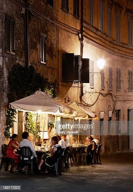 people dining outside restaurants at night - サンジミニャーノ ストックフォトと画像