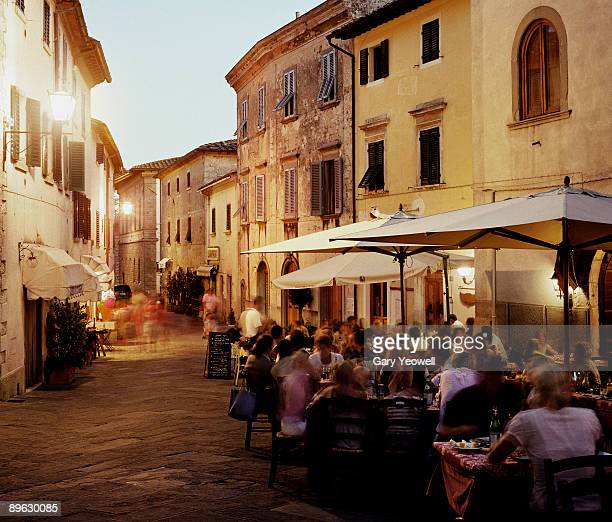 people dining outside restuarants at dusk - chianti region stock photos and pictures