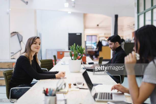 People discussing at desk in creative office