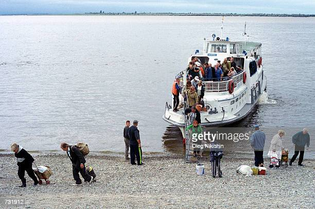 People disembark from a ferry August 30 2000 in Khabarovsk Russia's far East Many people have gardens on islands near Khabarovsk on the Amur River