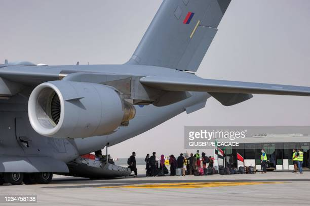 People disembark off a Royal Air Force Boeing C-17A Globemaster III military transport aircraft carrying evacuees from Afghanistan and arriving at...
