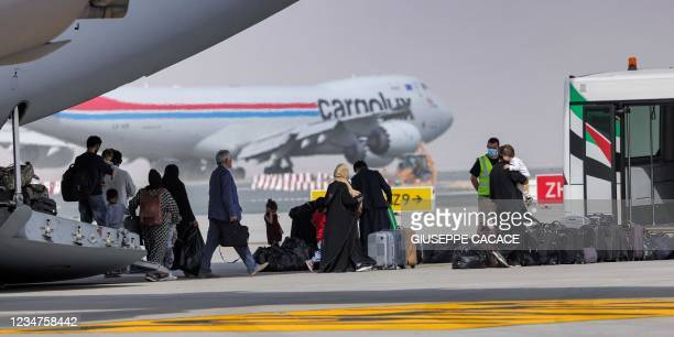 People disembark off a Royal Air Force military transport aircraft carrying evacuees from Afghanistan and arriving at Al-Maktoum International...