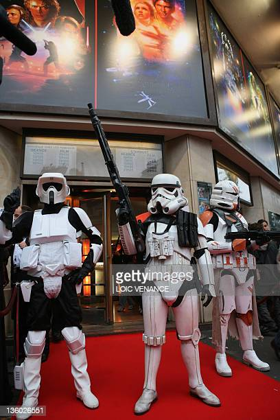 People disguised as characters of US director George Lucas films Star Wars queue in front of the Grand Rex cinema in Paris, 27 October 2007 to attend...