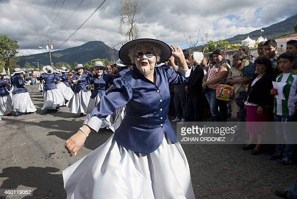 People disguised as elderly people take part in the '24 devils dance' during the Virgin of the Immaculate Conception celebrations on December 7 2014...