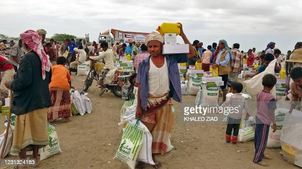 People displaced by conflict receive food aid donated by a Kuwaiti charity organisation in the village of Hays, near the conflict zone in Yemen's...