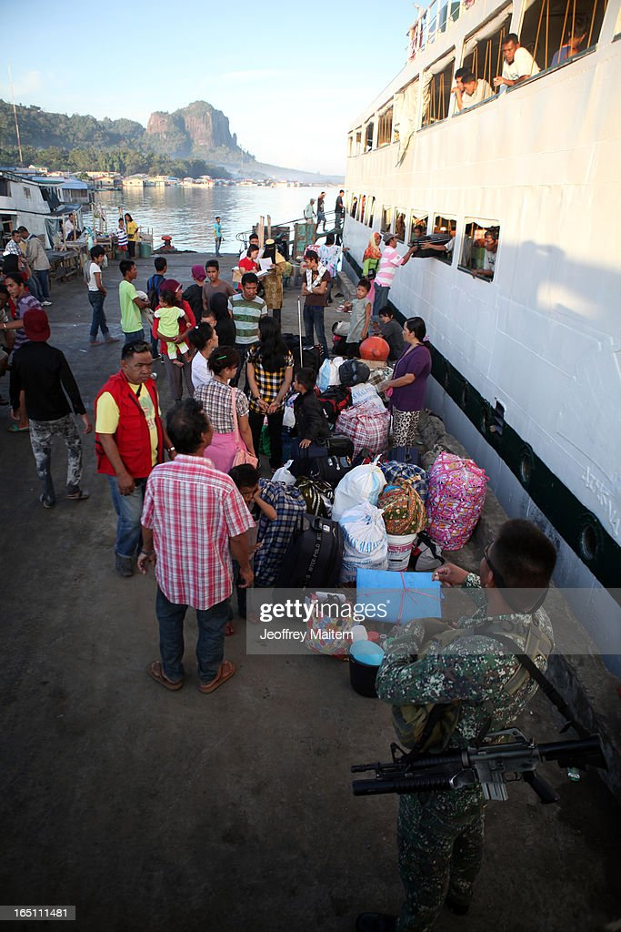 People displaced by continuing armed conflict between the supporters of Philippine Muslim clan Sulu Sultan Jamalul Kiram III and Royal Malaysian Police in Sabah, Malaysia, arrive at Bonggao Port on March 30, 2013 in Bonggao, Tawi-Tawi, Philippines. Following the insurgency in Sabah and the Malaysian government's subsequent crackdown on undocumented Filipinos, over 4000 people, mostly Filipino Muslims, have begun evacuating to the southern provinces of Basilan, Sulu, and Tawi-Tawi in the Philippines, with numbers expected to reach more than 100,000.