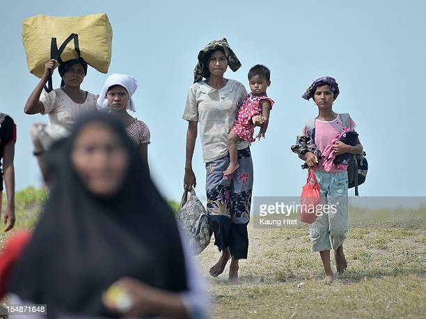 People displaced by the recent violence between Buddhist Rakhine and Muslim Rohingya in Kyuk Phyu township carry their belongings as they arrive to...
