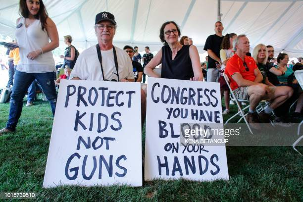 People display anti gun violence banners during a March for our Lives Rally at Fairfield Hills Campus in Newtown Connecticut on August 12 2018