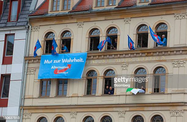 People display banners and flags out of building windows while Angela Merkel Germany's chancellor and party leader of the Christian Democratic Union...