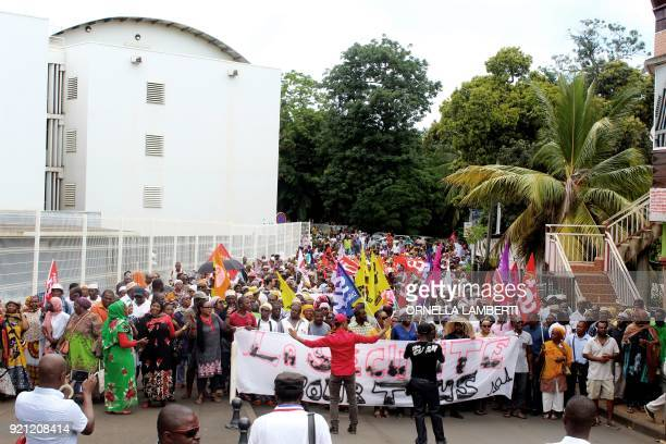 People display banners as they line up during a demonstration in Mamoudzou in the French overseas territory of Mayotte on February 20 2018 The...