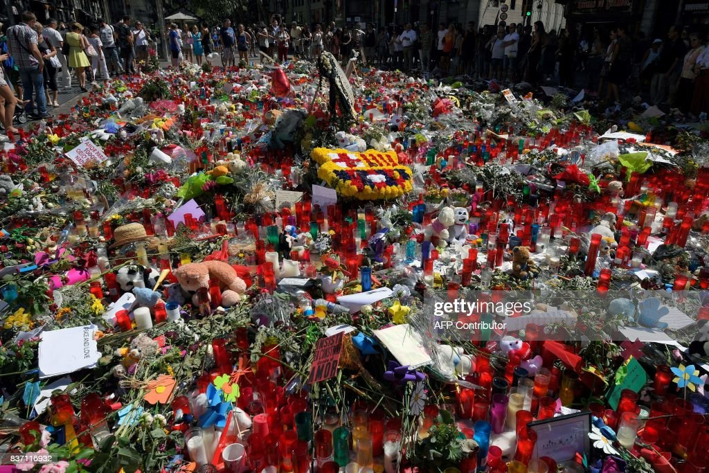 TOPSHOT - People display flowers and candles to pay tribute to the victims of the Barcelona and Cambrils attacks on the Rambla boulevard in Barcelona on August 22, 2017, five days after the attacks that killed 15 people. An alleged member of the terror cell that unleashed carnage in Spain last week admitted to a judge Tuesday that he and other suspects had planned a bigger attack, a judicial source said. /